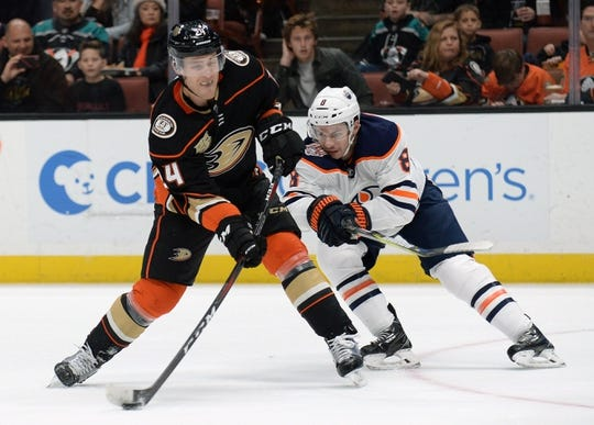 January 6, 2019; Anaheim, CA, USA; Anaheim Ducks right wing Carter Rowney (24) shoots on goal as Edmonton Oilers right wing Ty Rattie (8) moves in on defense during the second period at Honda Center. Mandatory Credit: Gary A. Vasquez-USA TODAY Sports