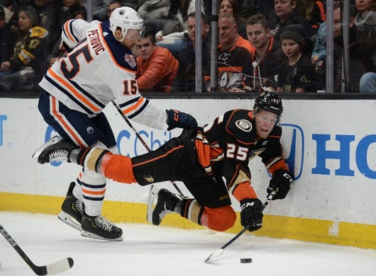 January 6, 2019; Anaheim, CA, USA; Anaheim Ducks right wing Ondrej Kase (25) is brought down by Edmonton Oilers defenseman Alexander Petrovic (15) during the second period at Honda Center. Mandatory Credit: Gary A. Vasquez-USA TODAY Sports