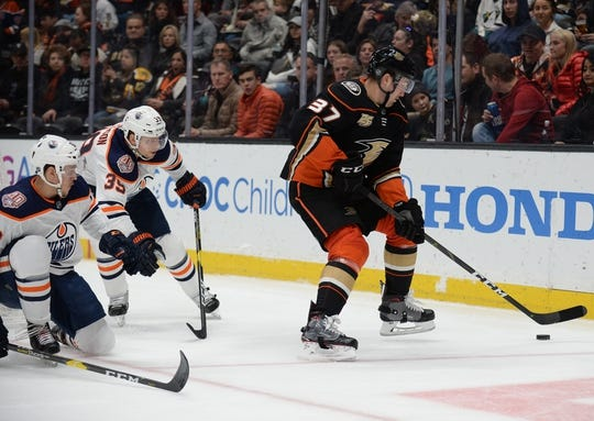 January 6, 2019; Anaheim, CA, USA; Anaheim Ducks left wing Nick Ritchie (37) moves the puck as Edmonton Oilers right wing Alex Chiasson (39) and defenseman Caleb Jones (82) move in to defend during the second period at Honda Center. Mandatory Credit: Gary A. Vasquez-USA TODAY Sports