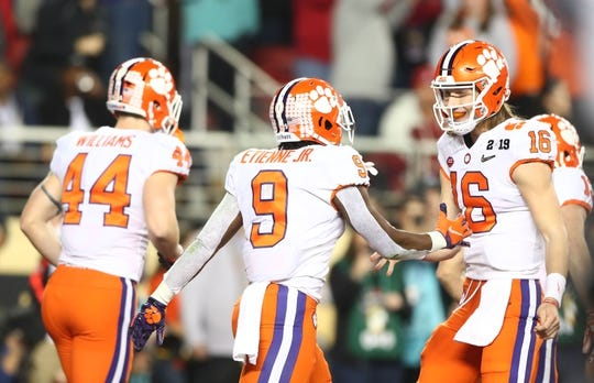 Jan 7, 2019; Santa Clara, CA, USA; Clemson Tigers running back Travis Etienne (9) celebrates with quarterback Trevor Lawrence (16) after scoring a touchdown against the Alabama Crimson Tide in the second quarter during the 2019 College Football Playoff Championship game at Levi's Stadium. Mandatory Credit: Mark Rebilas-USA TODAY Sports