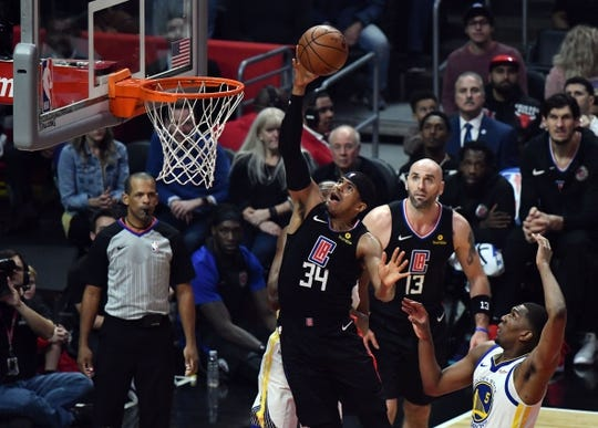 Jan 18, 2019; Los Angeles, CA, USA; Los Angeles Clippers forward Tobias Harris (34) puts up a shot past Golden State Warriors forward Draymond Green (hidden) and Golden State Warriors forward Kevon Looney (5) during the first quarter at Staples Center. Mandatory Credit: Robert Hanashiro-USA TODAY Sports