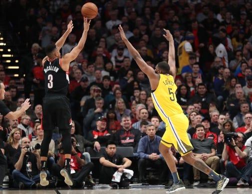 Feb 13, 2019; Portland, OR, USA; Portland Trail Blazers guard CJ McCollum (3) shoots over Golden State Warriors center Kevon Looney (5) in the first half at Moda Center. Mandatory Credit: Jaime Valdez-USA TODAY Sports
