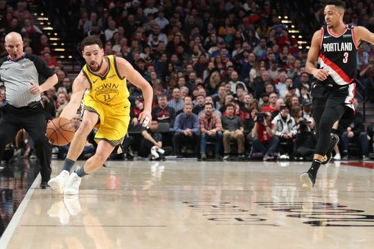 Feb 13, 2019; Portland, OR, USA;  Golden State Warriors guard Klay Thompson (11) prevents the ball from going out of bounds as Portland Trail Blazers guard CJ McCollum (3) looks on in the first half at Moda Center. Mandatory Credit: Jaime Valdez-USA TODAY Sports