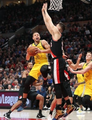Feb 13, 2019; Portland, OR, USA;  Golden State Warriors guard Stephen Curry (30) shoots into the arms of Portland Trail Blazers center Jusuf Nurkic (27) in the first half at Moda Center. Mandatory Credit: Jaime Valdez-USA TODAY Sports