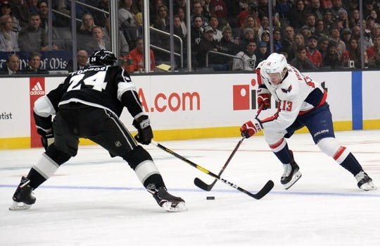 February 18, 2019; Los Angeles, CA, USA; Washington Capitals left wing Jakub Vrana (13) moves the puck against Los Angeles Kings defenseman Derek Forbort (24) during the first period at Staples Center. Mandatory Credit: Gary A. Vasquez-USA TODAY Sports
