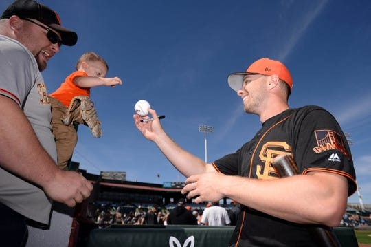 Mar 9, 2019; Scottsdale, AZ, USA; San Francisco Giants left fielder Austin Slater (53) hands a signed ball to 1-year old Hunter Sublow and father, Brian, of Petaluma, CA before the game against the Chicago Cubs at Scottsdale Stadium. Mandatory Credit: Orlando Ramirez-USA TODAY Sports