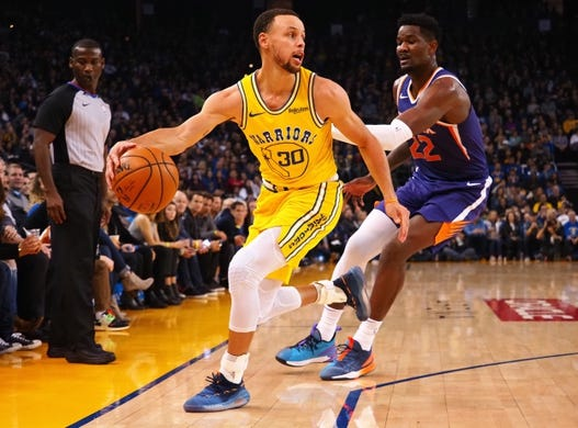 Mar 10, 2019; Oakland, CA, USA; Golden State Warriors guard Stephen Curry (30) chases down the loose ball ahead of Phoenix Suns center Deandre Ayton (22) during the first quarter at Oracle Arena. Mandatory Credit: Kelley L Cox-USA TODAY Sports