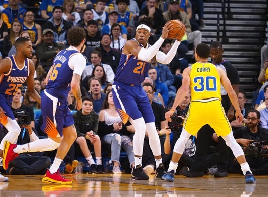 Mar 10, 2019; Oakland, CA, USA; Phoenix Suns forward Richaun Holmes (21) controls the ball against Golden State Warriors guard Stephen Curry (30) during the first quarter at Oracle Arena. Mandatory Credit: Kelley L Cox-USA TODAY Sports