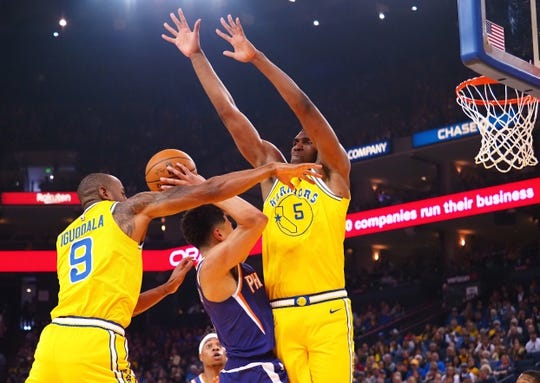 Mar 10, 2019; Oakland, CA, USA; Golden State Warriors guard Andre Iguodala (9) and center Kevon Looney (5) defend Phoenix Suns guard Devin Booker (1) during the first quarter at Oracle Arena. Mandatory Credit: Kelley L Cox-USA TODAY Sports