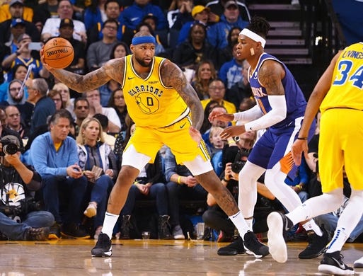 Mar 10, 2019; Oakland, CA, USA; Golden State Warriors center DeMarcus Cousins (0) controls the ball against Phoenix Suns forward Richaun Holmes (21) during the second quarter at Oracle Arena. Mandatory Credit: Kelley L Cox-USA TODAY Sports