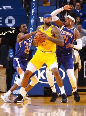 Mar 10, 2019; Oakland, CA, USA; Golden State Warriors center DeMarcus Cousins (0) controls the ball between Phoenix Suns forward Josh Jackson (20) and forward Richaun Holmes (21) during the second quarter at Oracle Arena. Mandatory Credit: Kelley L Cox-USA TODAY Sports