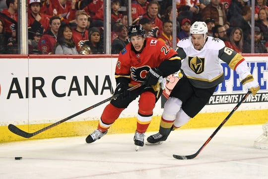Mar 10, 2019; Calgary, Alberta, CAN; Calgary Flames defenseman Travis Hamonic (24) moves the puck away from Las Vegas Golden Knights right wing Mark Stone (61) during the first period at Scotiabank Saddledome. Mandatory Credit: Candice Ward-USA TODAY Sports