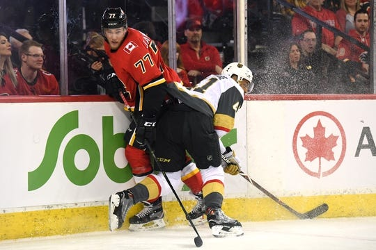 Mar 10, 2019; Calgary, Alberta, CAN; Calgary Flames center Mark Jankowski (77) collides with Las Vegas Golden Knights center Pierre-Edouard Bellemare (41) during the first period at Scotiabank Saddledome. Mandatory Credit: Candice Ward-USA TODAY Sports