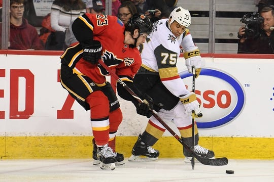 Mar 10, 2019; Calgary, Alberta, CAN; Calgary Flames center Sean Monahan (23) and Las Vegas Golden Knights right wing Ryan Reaves (75) battle for the puck in the first period at Scotiabank Saddledome. Mandatory Credit: Candice Ward-USA TODAY Sports