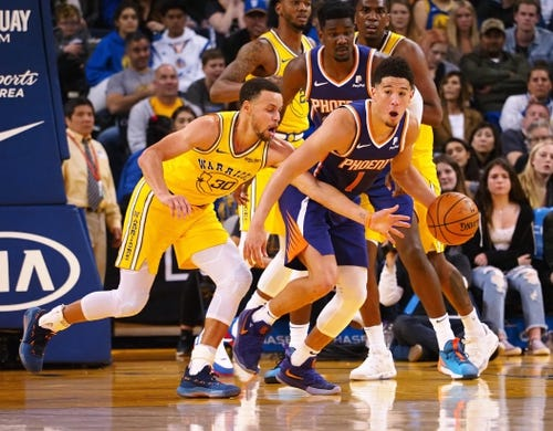 Mar 10, 2019; Oakland, CA, USA; Phoenix Suns guard Devin Booker (1) controls the ball ahead of Golden State Warriors guard Stephen Curry (30) during the third quarter at Oracle Arena. Mandatory Credit: Kelley L Cox-USA TODAY Sports