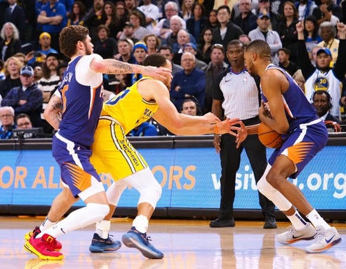 Mar 10, 2019; Oakland, CA, USA; Golden State Warriors guard Stephen Curry (30) loses the ball to Phoenix Suns forward Mikal Bridges (25) ahead of guard Tyler Johnson (16) during the fourth quarter at Oracle Arena. Mandatory Credit: Kelley L Cox-USA TODAY Sports
