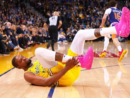Mar 10, 2019; Oakland, CA, USA; Golden State Warriors forward Kevin Durant (35) goes down with an injury holding his right ankle during the fourth quarter against the Phoenix Suns at Oracle Arena. Mandatory Credit: Kelley L Cox-USA TODAY Sports