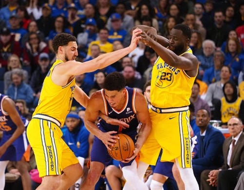 Mar 10, 2019; Oakland, CA, USA; Phoenix Suns guard Devin Booker (1) controls the ball between Golden State Warriors guard Klay Thompson (11) and forward Draymond Green (23) during the fourth quarter at Oracle Arena. Mandatory Credit: Kelley L Cox-USA TODAY Sports