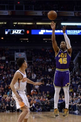 Mar 13, 2019; Phoenix, AZ, USA; Utah Jazz guard Donovan Mitchell (45) shoots over Phoenix Suns guard Devin Booker (1) during the first half at Talking Stick Resort Arena. Mandatory Credit: Joe Camporeale-USA TODAY Sports