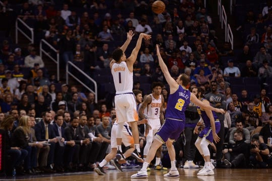 Mar 13, 2019; Phoenix, AZ, USA; Phoenix Suns guard Devin Booker (1) shoots over Utah Jazz forward Joe Ingles (2) during the first half at Talking Stick Resort Arena. Mandatory Credit: Joe Camporeale-USA TODAY Sports