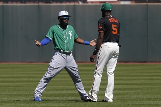 Mar 17, 2019; Scottsdale, AZ, USA; Kansas City Royals center fielder Brian Goodwin (25) talks to San Francisco Giants centerfielder Cameron Maybin (5) before a spring training game at Scottsdale Stadium. Mandatory Credit: Rick Scuteri-USA TODAY Sports