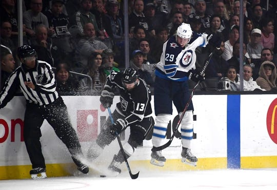 Mar 18, 2019; Los Angeles, CA, USA; Los Angeles Kings left wing Kyle Clifford (13) and Winnipeg Jets right wing Patrik Laine (29) battle for the puck in the first period at Staples Center. Mandatory Credit: Kirby Lee-USA TODAY Sports