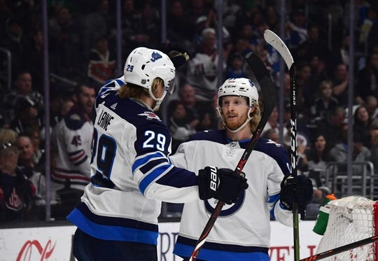 Mar 18, 2019; Los Angeles, CA, USA; Winnipeg Jets left wing Kyle Connor (81) celebrates with right wing Patrik Laine (29) after scoring a goal against the Los Angeles Kings in the first period at Staples Center. Mandatory Credit: Kirby Lee-USA TODAY Sports