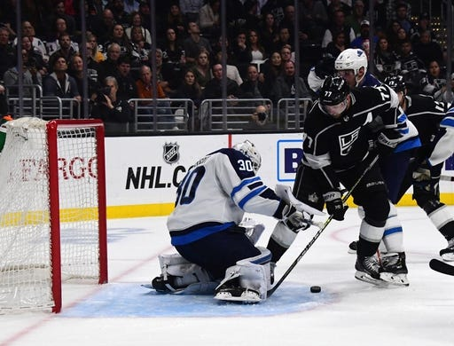 Mar 18, 2019; Los Angeles, CA, USA; Winnipeg Jets goaltender Laurent Brossoit (30) and defenseman Dmitry Kulikov (5) defend the goal against Los Angeles Kings center Jeff Carter (77)  in the second period at Staples Center. Mandatory Credit: Kirby Lee-USA TODAY Sports