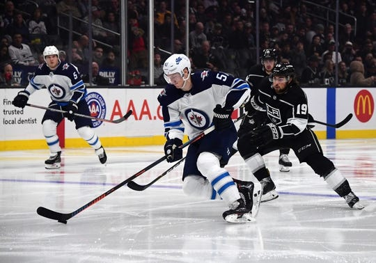 Mar 18, 2019; Los Angeles, CA, USA;  Winnipeg Jets defenseman Tyler Myers (57) is pursued by Los Angeles Kings left wing Alex Iafallo (19) in the second period at Staples Center. Mandatory Credit: Kirby Lee-USA TODAY Sports