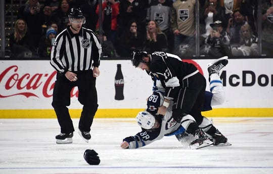 Mar 18, 2019; Los Angeles, CA, USA; Los Angeles Kings left wing Kyle Clifford (13) and Winnipeg Jets defenseman Nathan Beaulieu (88) fight in the third period at Staples Center. The Jets defeated the Kings 3-2. Mandatory Credit: Kirby Lee-USA TODAY Sports