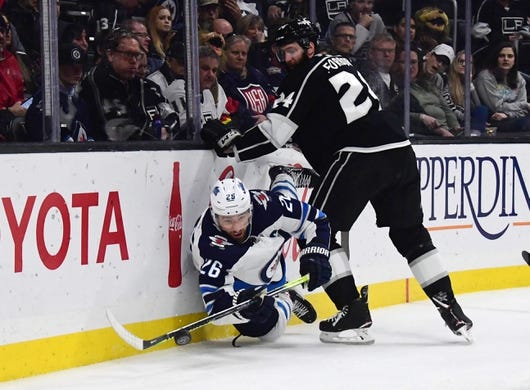 Mar 18, 2019; Los Angeles, CA, USA; Los Angeles Kings defenseman Derek Forbort (24) and Winnipeg Jets right wing Blake Wheeler (26) battle for the puck  in the third period at Staples Center. The Jets defeated the Kings 3-2. Mandatory Credit: Kirby Lee-USA TODAY Sports