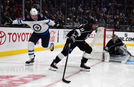 Mar 18, 2019; Los Angeles, CA, USA; Los Angeles Kings center Anze Kopitar (11) and Winnipeg Jets right wing Patrik Laine (29) battle for the puck in the third period at Staples Center. The Jets defeated the Kings 3-2. Mandatory Credit: Kirby Lee-USA TODAY Sports