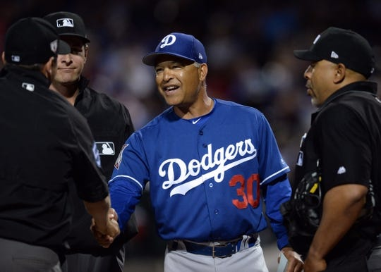 Mar 20, 2019; Mesa, AZ, USA; Los Angeles Dodgers manager Dave Roberts (30) shakes hands with umpires prior to the game against the Chicago Cubs at Sloan Park. Mandatory Credit: Joe Camporeale-USA TODAY Sports