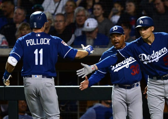 Mar 20, 2019; Mesa, AZ, USA; Los Angeles Dodgers center fielder A.J. Pollock (11) slaps hands with Los Angeles Dodgers shortstop Corey Seager (5) and Los Angeles Dodgers manager Dave Roberts (30) after hitting a home run against the Chicago Cubs during the first inning at Sloan Park. Mandatory Credit: Joe Camporeale-USA TODAY Sports