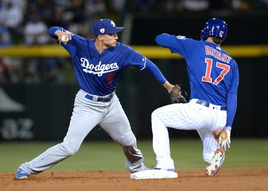 Mar 20, 2019; Mesa, AZ, USA; Los Angeles Dodgers shortstop Corey Seager (5) throws to first after forcing out Chicago Cubs third baseman Kris Bryant (17) at second during the first inning at Sloan Park. Mandatory Credit: Joe Camporeale-USA TODAY Sports