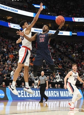 Mar 21, 2019; Salt Lake City, UT, USA; Fairleigh Dickinson Knights forward Kaleb Bishop (12) shoots against Gonzaga Bulldogs guard Josh Perkins (13) in the first half in the first round of the 2019 NCAA Tournament at Vivint Smart Home Arena. Mandatory Credit: Kirby Lee-USA TODAY Sports