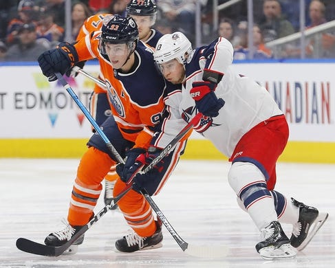 Mar 21, 2019; Edmonton, Alberta, CAN; Edmonton Oilers forward Ryan Nugent-Hopkins (93) and Columbus Blue Jackets forward Cam Atkinson (13) battle for a loose puck during the first period at Rogers Place. Mandatory Credit: Perry Nelson-USA TODAY Sports