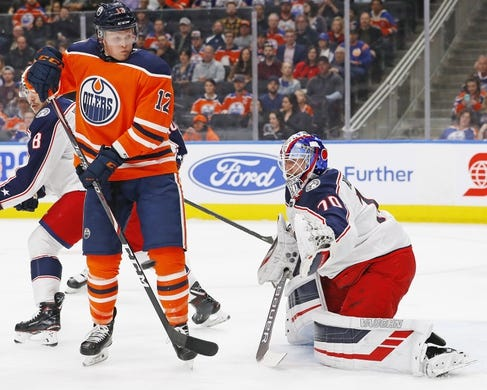 Mar 21, 2019; Edmonton, Alberta, CAN; Edmonton Oilers forward Colby Cave (12)  tries to screen Columbus Blue Jackets goaltender Joonas Korpisalo (70) during the first period at Rogers Place. Mandatory Credit: Perry Nelson-USA TODAY Sports