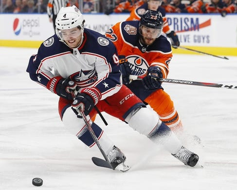 Mar 21, 2019; Edmonton, Alberta, CAN; Edmonton Oilers forward Tobias Rieder (22) chases Columbus Blue Jackets defensemen Scott Harrington (4) for a loose puck during the first period at Rogers Place. Mandatory Credit: Perry Nelson-USA TODAY Sports