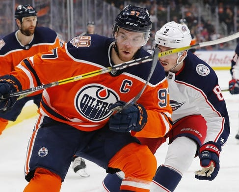Mar 21, 2019; Edmonton, Alberta, CAN; Edmonton Oilers forward Connor McDavid (97) and Columbus Blue Jackets defensemen Zack Werenski (8) battle for a loose puck during the first period at Rogers Place. Mandatory Credit: Perry Nelson-USA TODAY Sports