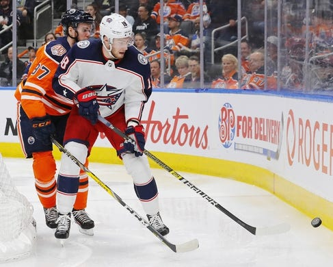 Mar 21, 2019; Edmonton, Alberta, CAN; Edmonton Oilers forward Connor McDavid (97) and Columbus Blue Jackets forward Pierre-Luc Bubois (18) battle for a loose puck during the second period at Rogers Place. Mandatory Credit: Perry Nelson-USA TODAY Sports
