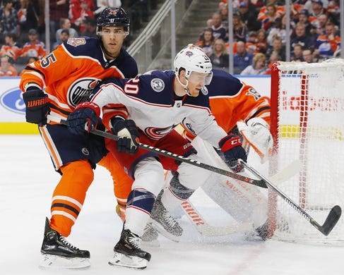 Mar 21, 2019; Edmonton, Alberta, CAN;  Edmonton Oilers defensemen Darnell Nurse (25) checks Columbus Blue Jackets forward Riley Nash (20) in front of the Edmonton Oilers net during the second period at Rogers Place. Mandatory Credit: Perry Nelson-USA TODAY Sports