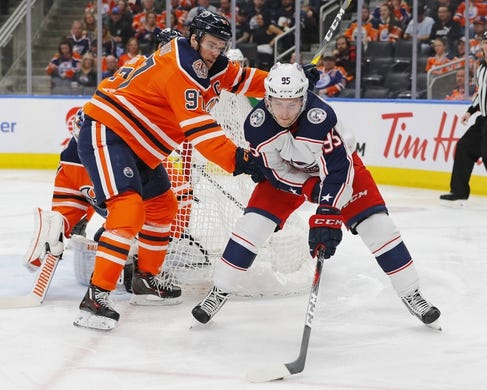 Mar 21, 2019; Edmonton, Alberta, CAN; Edmonton Oilers forward Connor McDavid (97) and Columbus Blue Jackets forward Matt Duchene (95) battle for a loose puck during the second period at Rogers Place. Mandatory Credit: Perry Nelson-USA TODAY Sports