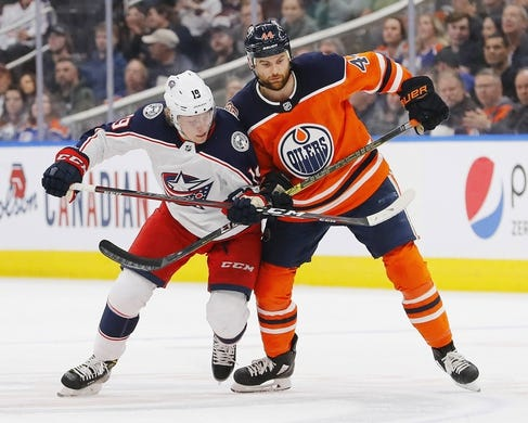 Mar 21, 2019; Edmonton, Alberta, CAN; Columbus Blue Jackets forward Ryan Dzingel (19) and Edmonton Oilers forward Zack Kassian (44) look for a loose puck during the second period at Rogers Place. Mandatory Credit: Perry Nelson-USA TODAY Sports