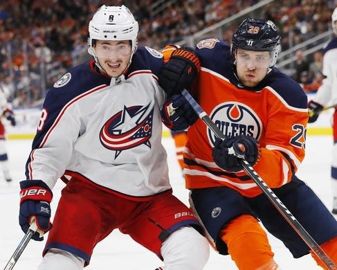 Mar 21, 2019; Edmonton, Alberta, CAN; Columbus Blue Jackets defensemen Zack Werenski (8) and Edmonton Oilers forward Leon Draisaitl (29) battle for position during the third period at Rogers Place. Mandatory Credit: Perry Nelson-USA TODAY Sports