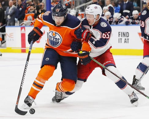 Mar 21, 2019; Edmonton, Alberta, CAN; Columbus Blue Jackets defensemen Markus Nutivaara (65) tries to knock Edmonton Oilers forward Leon Draisaitl (29) of the puck during the third period at Rogers Place. Mandatory Credit: Perry Nelson-USA TODAY Sports