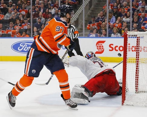 Mar 21, 2019; Edmonton, Alberta, CAN; Edmonton Oilers forward Connor McDavid (97) scores a third period goal against Columbus Blue Jackets goaltender Joonas Korpisalo (70) at Rogers Place. Mandatory Credit: Perry Nelson-USA TODAY Sports
