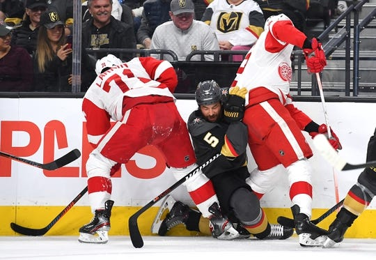 Mar 23, 2019; Las Vegas, NV, USA; Vegas Golden Knights defenseman Deryk Engelland (5) falls between Detroit Red Wings center Dylan Larkin (71) and Detroit Red Wings right wing Anthony Mantha (39) during the first period at T-Mobile Arena. Mandatory Credit: Stephen R. Sylvanie-USA TODAY Sports