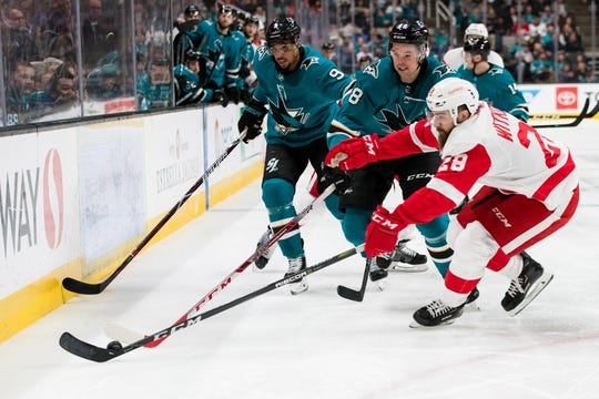 Mar 25, 2019; San Jose, CA, USA; Detroit Red Wings right wing Luke Witkowski (28) and San Jose Sharks center Tomas Hertl (48) and left wing Evander Kane (9) battle for possession in the second period at SAP Center at San Jose. Mandatory Credit: John Hefti-USA TODAY Sports