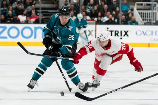 Mar 25, 2019; San Jose, CA, USA; San Jose Sharks right wing Timo Meier (28) and Detroit Red Wings center Christoffer Ehn (70) battle for possession in the second period at SAP Center at San Jose. Mandatory Credit: John Hefti-USA TODAY Sports